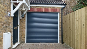 Anthracite roller garage door with white frame to match front door