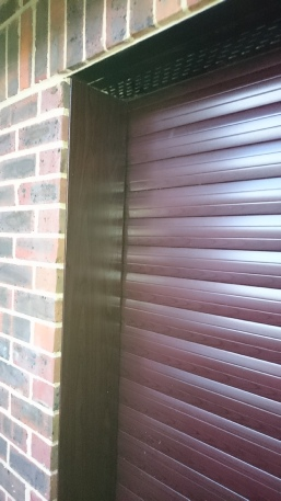Rowewood roller door, Optima 77 with rosewood clad reveals.